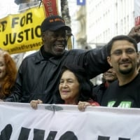 Bonnie Raitt, actor Danny Glover and Dolores Huerta (co-founder of the United Farmworkers Union) greeted marchers as they walked up Market Street in San Francisco's huge anti-war march. - February 17, 2003  © Scott Sommerdorf /San Francisco Chronicle/Corbis