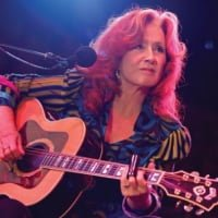 Raitt picks her Guild while on tour with Taj Mahal at the Telluride Blues and Brews Festival in the fall of 2009. © Barry Brecheisen