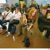 "Tom Waits (far right), Bonnie Raitt, Norton Buffalo, Austin Willacy and Jason Newsted - Bonnie Raitt told the kids at Spring Valley Elementary about learning guitar when she was 8 years old. Her hands weren't large enough to span the fretboard and make an F chord, so she learned to do it with her thumb.  ""Tell Bonnie what we call the F chord,"" said their guitar teacher, Laura Chinn-Smoot.  ""The ouch chord,"" a couple of dozen young public school guitar students said in unison.  Raitt inveigled her old pal Tom Waits to join her on piano and sing a duet of ""Sweet and Shiny Eyes,"" a song they knew from touring together a few years back when Jerry Ford was still president. Former Metallica bassist Jason Newsted, currently playing with Ozzy Osbourne, picked up his bass, and Norton Buffalo added a little harmonica . . . Raitt, Waits, Buffalo jam with S.F. schoolkids - 10/21/2003  ©	David Paul Morris"